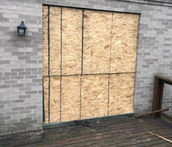 wooden board over screen door after break in