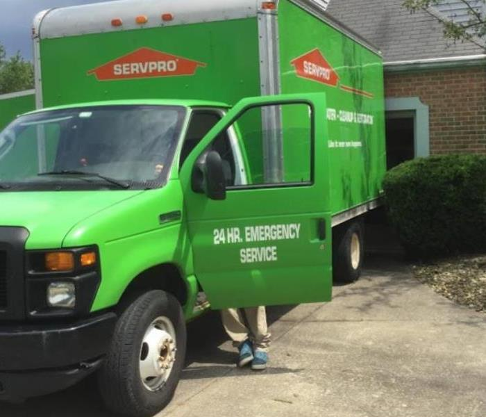 green van with driver door open outside of residential home