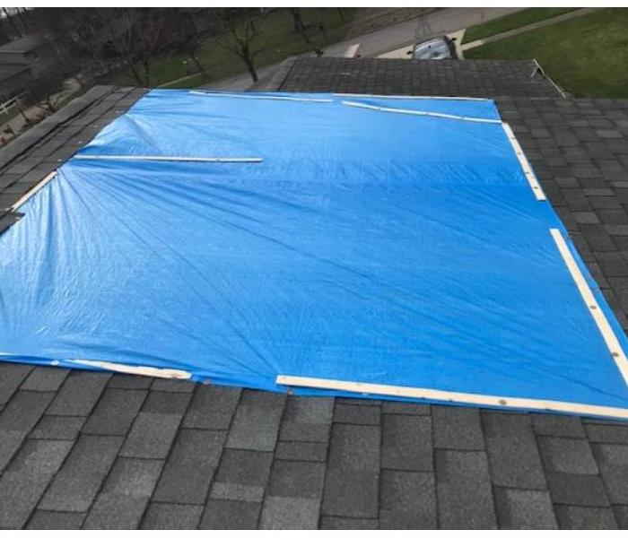 blue tarp on roof after storm damage