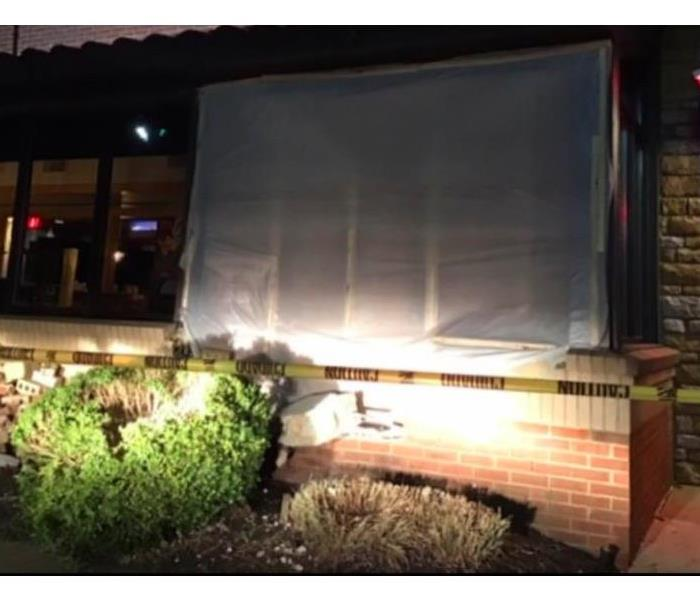 tarp over section of restaurant that was hit by a car