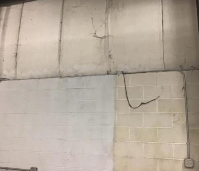dust and debris buildup on white walls in commercial warehouse