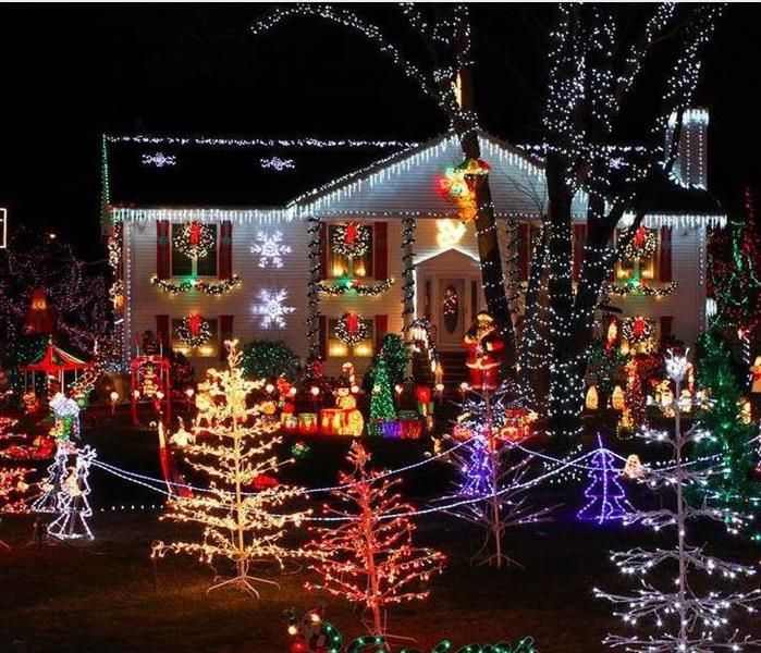 Christmas lights on house and in yard of house