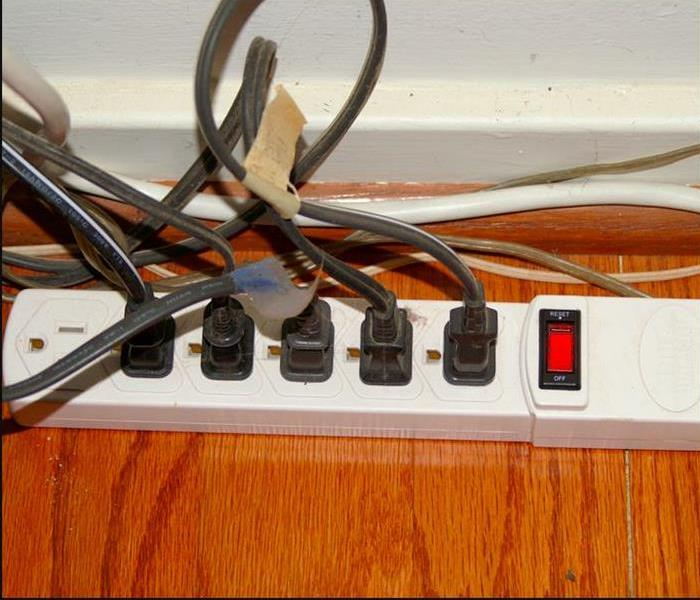 power strip on hardwood floor with multiple plugs plugged into it
